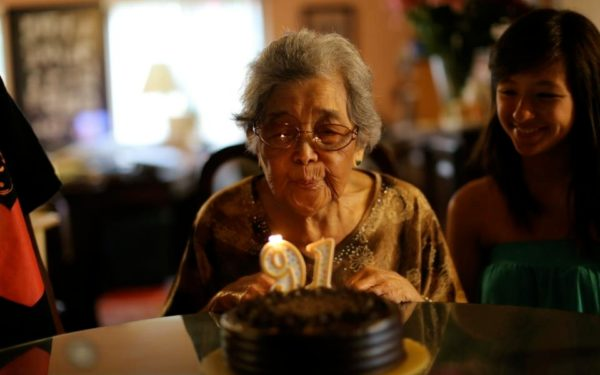grandmother blowing candles out on birthday cake