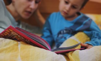 mom reading to son in bed - single parent finances