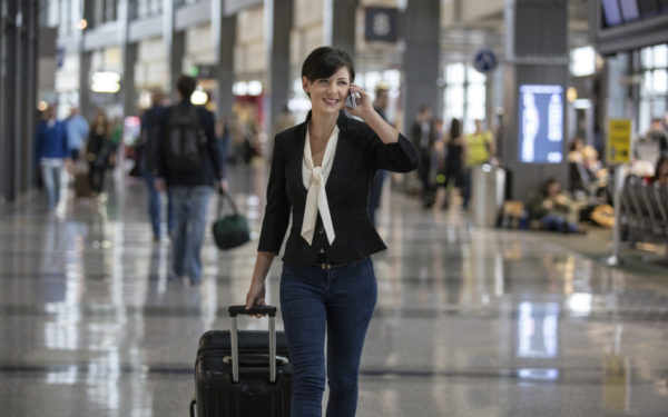businesswoman walking through airport talking on phone and pulling luggage