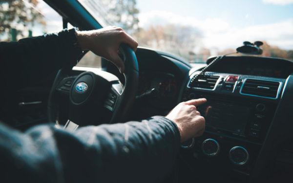 man changing radio in car