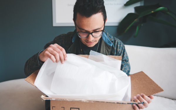 man opening amazon delivery box - save money on subscriptions