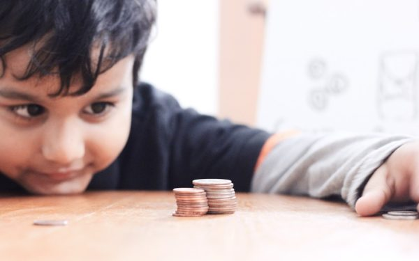 kid looking at a stack of coins on the table learning about compound interest for kids