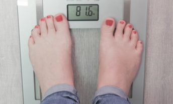 woman stepping on scale - check your credit report more often