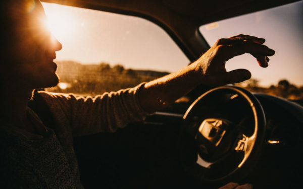 man driving at sunset - non owner car insurance