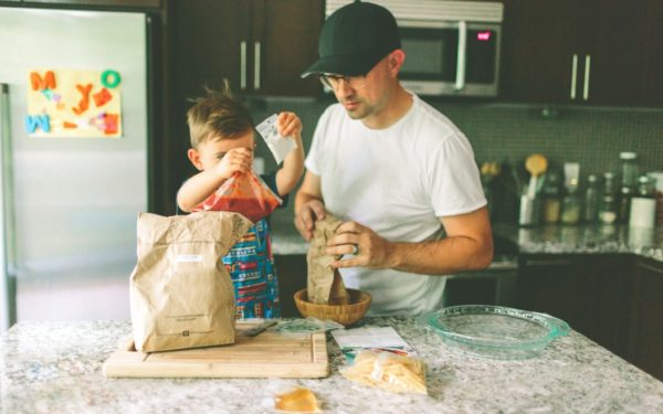 father and child preparing a meal in the kitchen