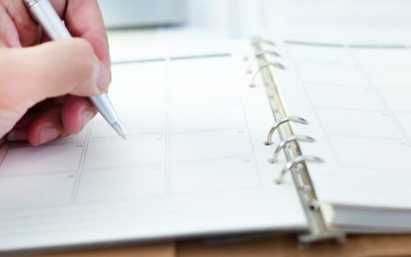 woman writing in weekly planner