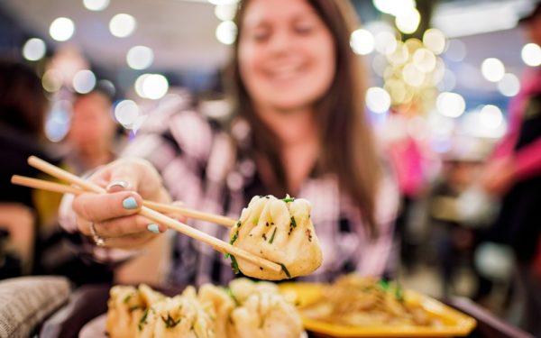 woman eating with chopsticks at restaurant