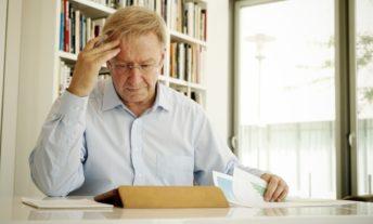 worried retired man reviewing paperwork