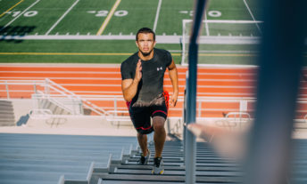 man running up the bleacher stairs toward a goal