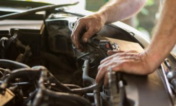 mechanic working under hood to fix car - fix your credit to save money on car insurance