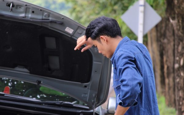 man looking at hood of broken down car