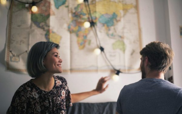 couple talking in front of map - investing for medium term goals