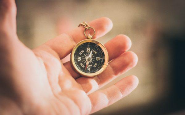 holding a compass in hand - guiding principles