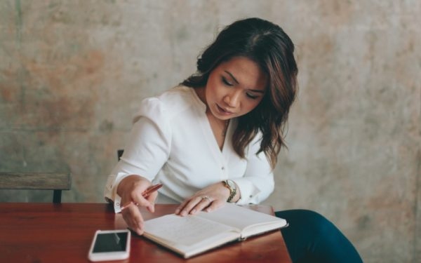 business woman writing notes at table - investment checklist