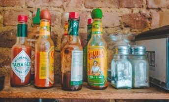a collection of hot sauce bottles at a restaurant