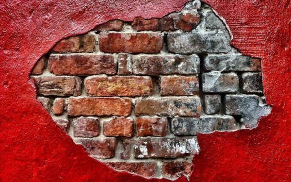 red wall with exposed brick wall underneath - firewall and diversification