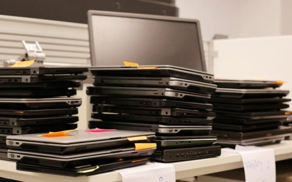old laptops on a table in office ready to be repaired