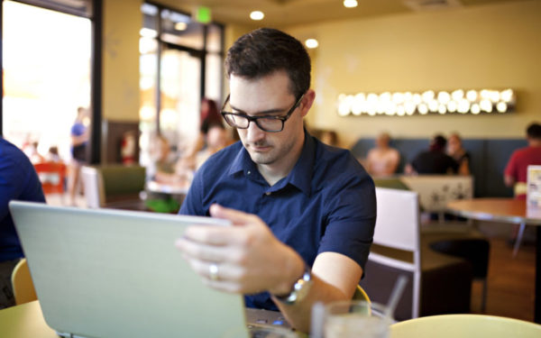 man working on laptop at coffeeshop looking for best personal loans online