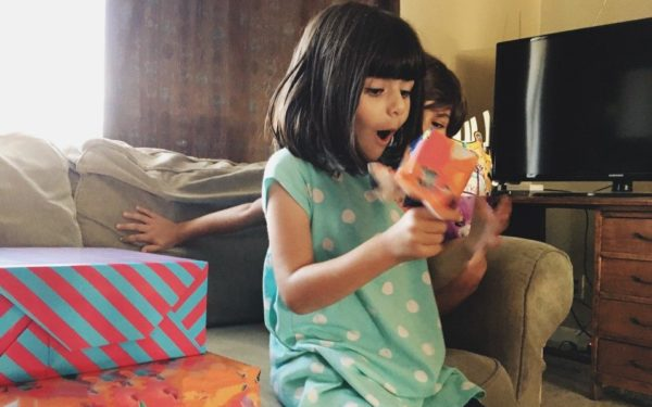 girl opening a gift with excitement - money gift ideas for kids and best stocks for kids