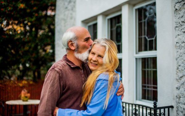 retired couple hugging outside their home - reverse mortgages