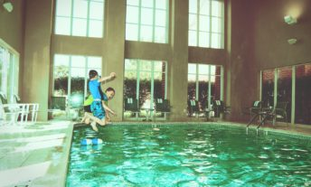kids jumping into a hotel pool - redeeming travel rewards points when you can't afford to travel