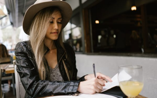 woman signing credit card receipt at restaurant