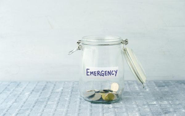 a nearly empty money jar marked emergency fund