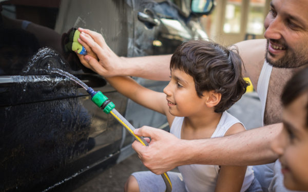kids washing car in driveway