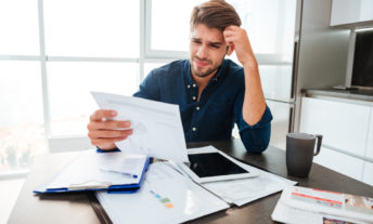 confused man reviewing credit report