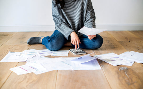 woman with many bill statements on the floor - will consolidating student loans help my credit score
