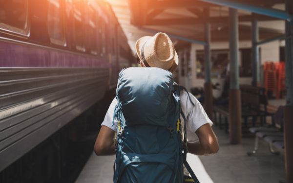 man carrying backpack at train station
