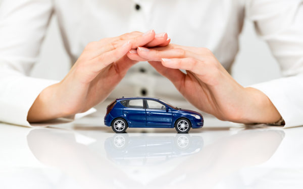 woman protecting toy car with hands - car insurance