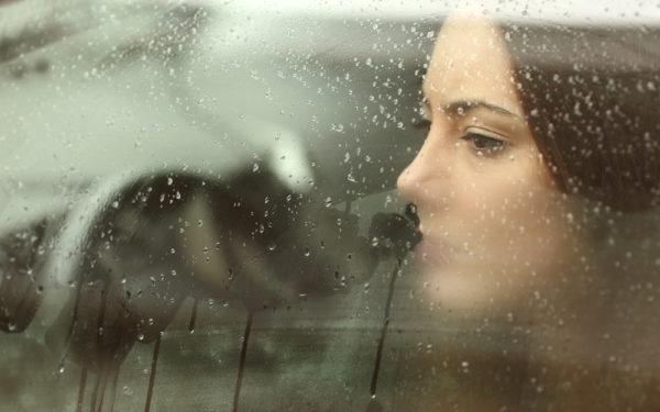 melancholy woman looking out the window in the rain