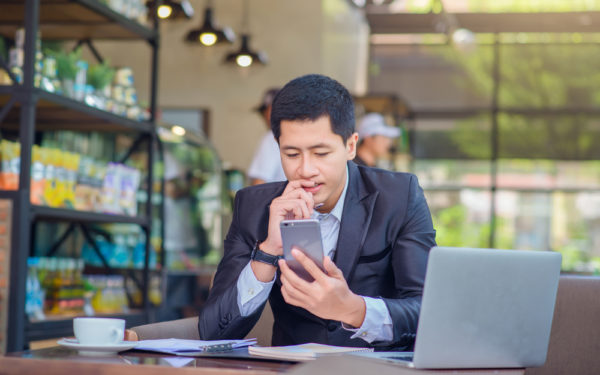 man looking at phone and thinking in coffee shop with laptop