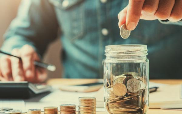 man saving money in a jar