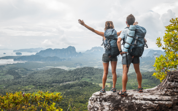Man and woman hikers standing on top of a small mountain