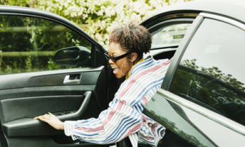 Woman getting out of car with big smile on face