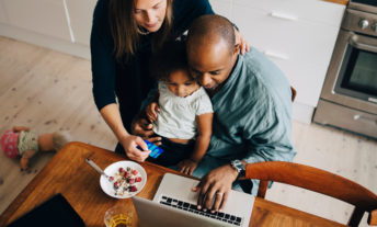 Parents with daughter shopping online on laptop at dining room