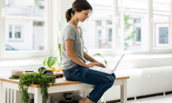 Woman sitting on kitchen table using laptop