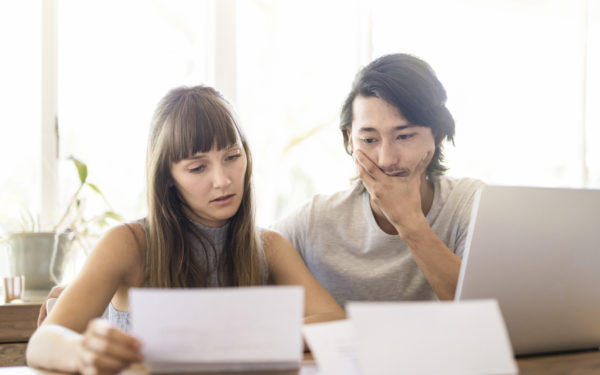 Woman and man in front of laptop with bills