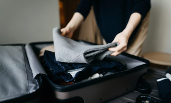 Woman packing a suitcase on bed for a trip at home