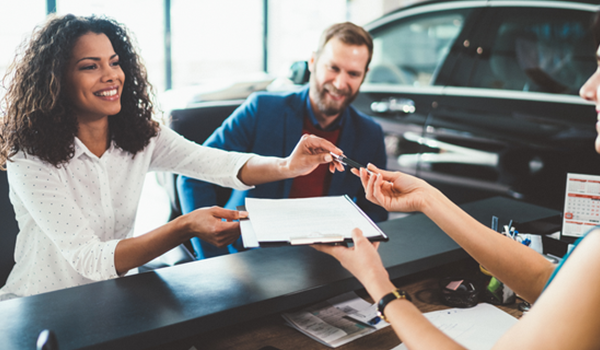 Man and woman signing paperwork for a car