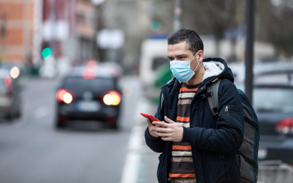 man in facemask hailing a rideshare