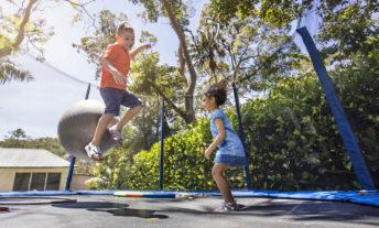 Aboriginal children bouncing on the trampoline in the backyard garden.