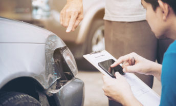 Man Holding Mobile Phone And Paper By Customer Showing Damaged Car