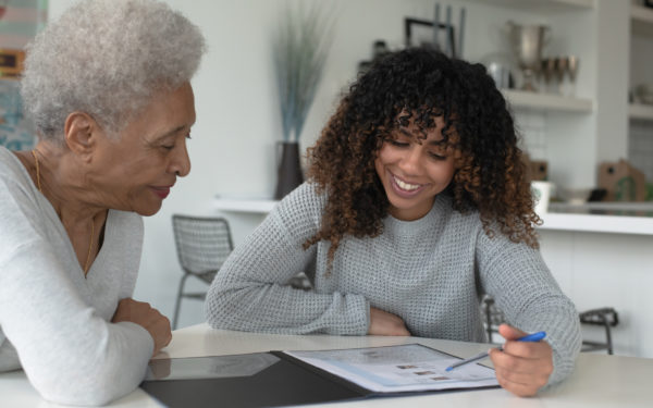 An African American adviser meets with an elderly client to discuss her financial plan, life insurance, or medicare needs. They are both dressed in casual clothing and meeting at a table in the clients home. It is a very neutral color pallet with whites and grays. The client and the adviser are both looking down at the documents on the table.