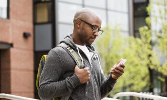 man using cell phone on city street